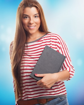 Jolie femme brune posant avec bloc-notes
