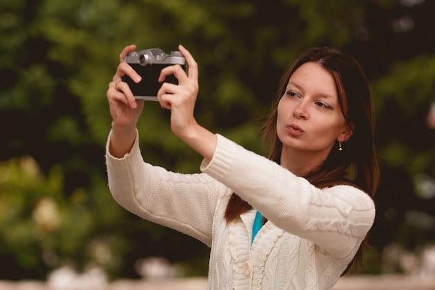 Jolie femme brune prenant une photo dans un parc