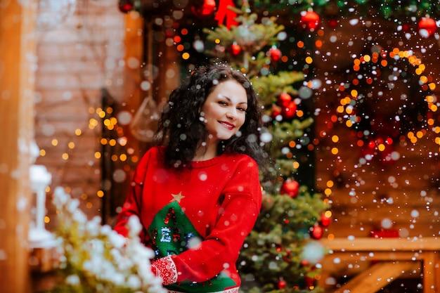 Jolie femme brune en pull de noël rouge posant sur la terrasse en bois ouverte