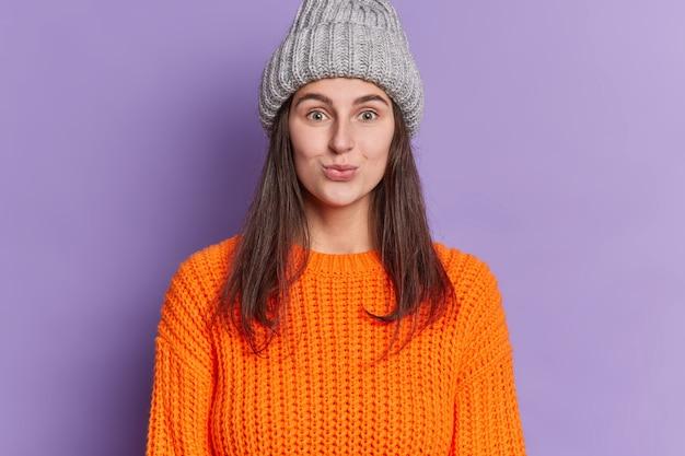 Jolie femme brune regarde avec des lèvres de moue d'expression drôle porte le pull orange tricoté chapeau gris bénéficie de la saison d'hiver.