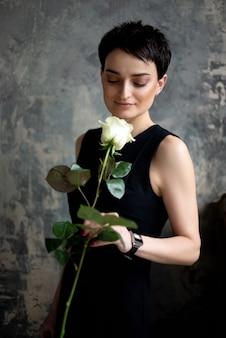 Jolie femme brune en robe noire tient une rose blanche dans sa main.