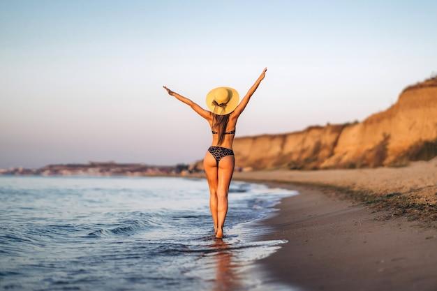 Jolie femme brune se détendre sur la plage à la mer.