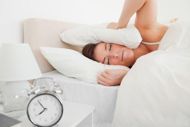 Jolie femme brune se réveiller avec une horloge en position couchée