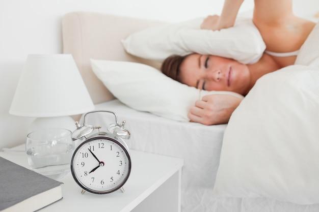 Jolie femme brune, se réveiller avec une horloge en position couchée
