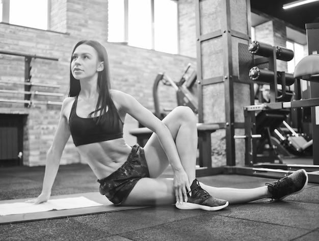 Jolie femme brune sexy en tenue de sport faisant des exercices d'étirement pour le corps tout en étant assis sur un tapis dans une salle de sport