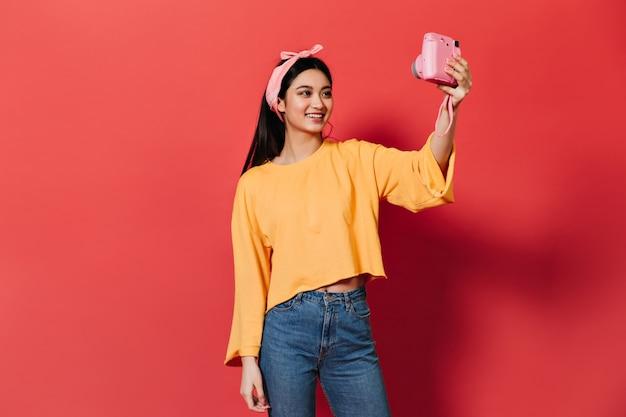 Jolie femme brune sourit et fait selfie sur le devant rose