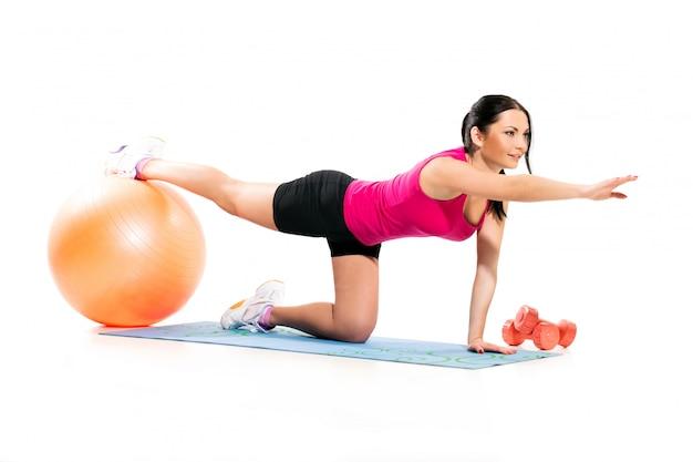Jolie femme brune sur le tapis d'exercice