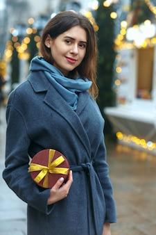 Jolie femme brune tenant une boîte-cadeau près de la foire de noël