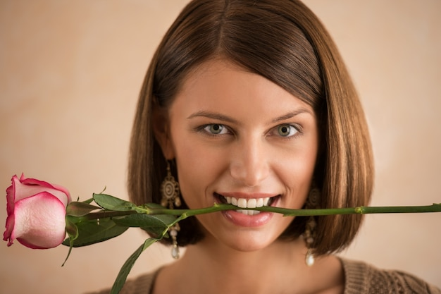 Jolie femme brune tenant rose dans sa bouche
