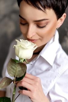 Jolie femme brune tient une rose blanche dans sa main gros plan portrait.