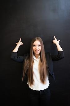 Jolie femme de bureau pointant vers le fond sur le tableau avec une expression de visage réfléchie. levant les doigts. les doigts comme un geste d'arme à feu, le visage surpris. pensées de la femme.