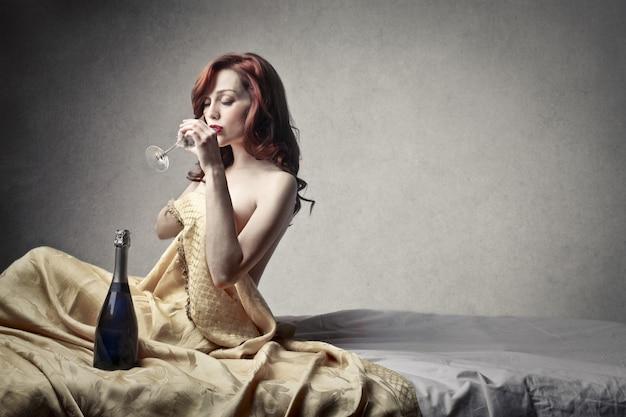 Jolie femme buvant du champagne au lit