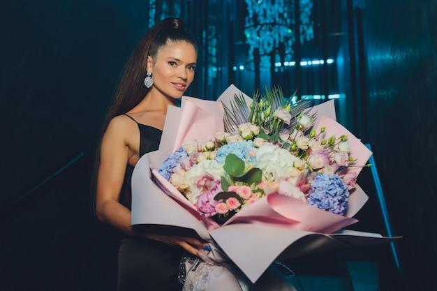 Jolie femme a un cadeau pour sa fête d'anniversaire et des fleurs pour prendre une bonne photo