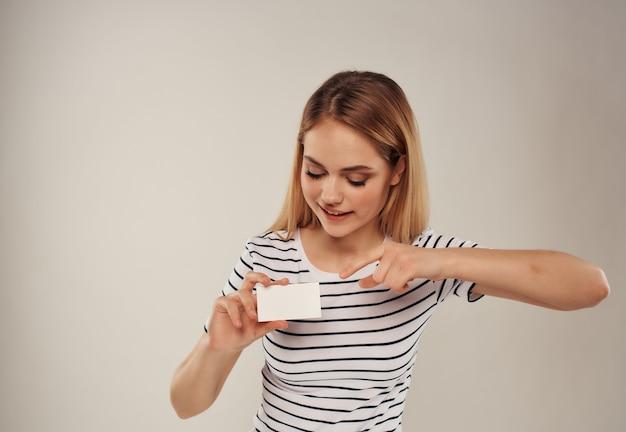 Jolie femme avec une carte de visite dans l'espace de copie à la main