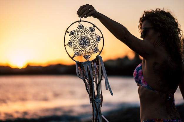 Jolie femme caucasienne d'âge moyen prendre un dreamcatcher fait à la main. plage en plein air coucher de soleil coloré activité de loisirs pittoresque. concept de vacances et d'envie de voyager. cheveux bouclés et lunettes de soleil pour voyager l