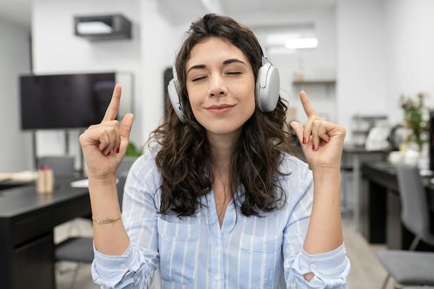 Jolie femme caucasienne aux cheveux noirs avec des écouteurs faisant un appel vidéo