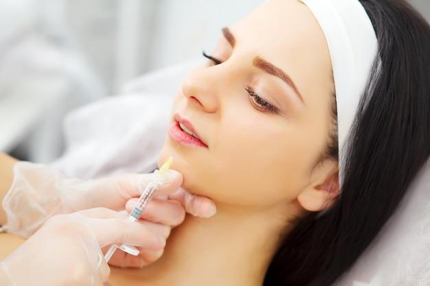 Jolie femme caucasienne ayant une injection d'acide hyaluronique dans la zone du visage