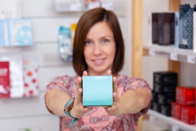 Jolie femme caucasienne avec boîte de crème pour le visage dans une boutique de cosmétiques