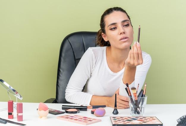 Jolie femme caucasienne confiante assise à table avec des outils de maquillage en regardant l'eye-liner