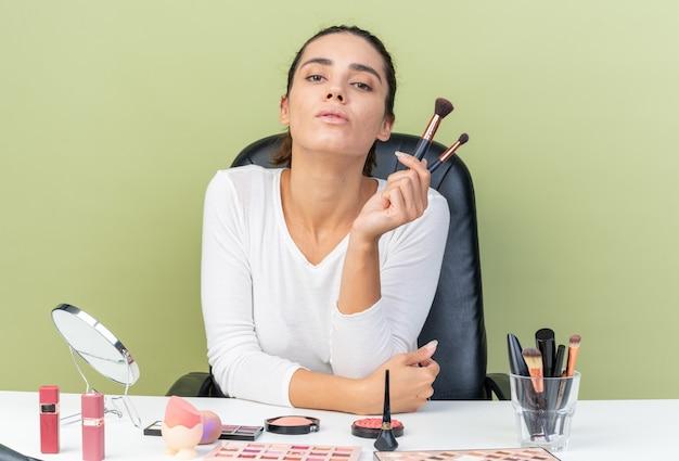 Jolie femme caucasienne confiante assise à table avec des outils de maquillage tenant des pinceaux de maquillage