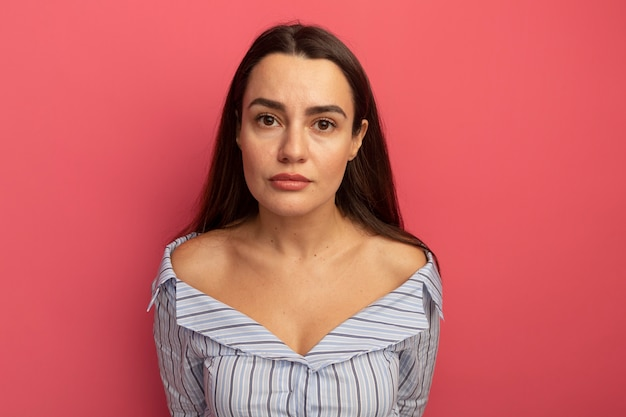 Jolie femme caucasienne confiante regarde la caméra sur rose