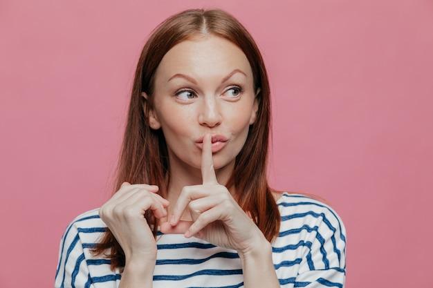 Jolie femme caucasienne curieuse fait signe de silence, garde l'index sur la bouche