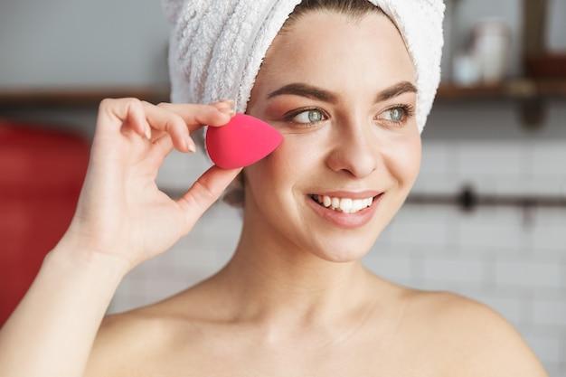 Jolie femme caucasienne enveloppée dans une serviette blanche appliquant du maquillage avec une éponge cosmétique dans l'appartement