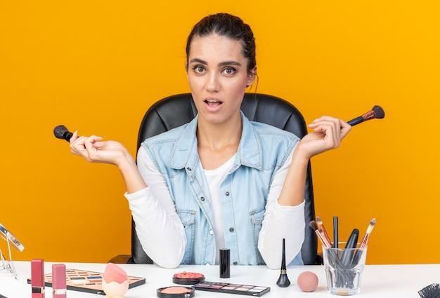 Jolie femme caucasienne excitée assise à table avec des outils de maquillage tenant des pinceaux de maquillage
