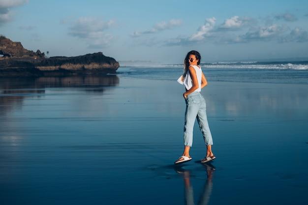 Jolie femme caucasienne en haut blanc et jeans sur la plage réfléchissante par l'océan au coucher du soleil