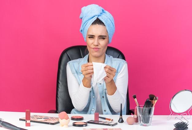 Jolie femme caucasienne mécontente aux cheveux enveloppés dans une serviette assise à table avec des outils de maquillage tenant une serviette d'insertion isolée sur un mur rose avec un espace de copie