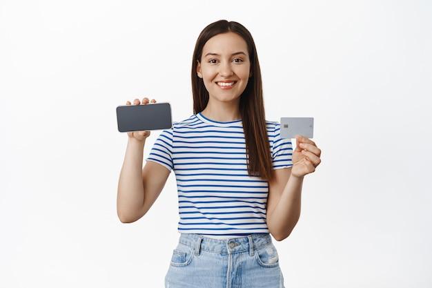 Jolie femme caucasienne montrant un écran de smartphone horizontal, un téléphone portable retourné et une carte de crédit, un concept publicitaire, un mur blanc