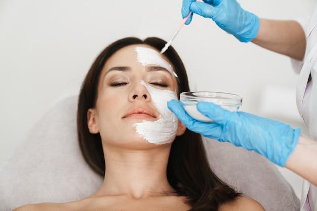 Jolie femme caucasienne obtenant une procédure cosmétique par un spécialiste en position couchée dans un salon de beauté