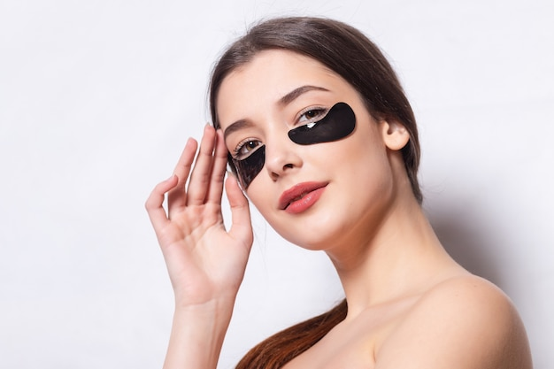 Jolie femme caucasienne en peignoir et serviette posant avec des taches noires regarde la caméra, industrie de la beauté, soins de la peau