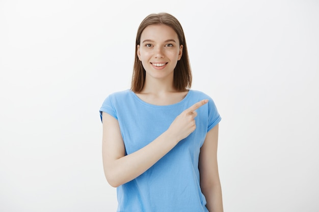 Jolie femme caucasienne pointant dans le coin supérieur droit et souriant, invitant à vérifier l'offre promotionnelle, bannière de réduction spéciale