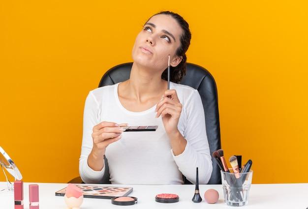 Jolie femme caucasienne réfléchie assise à table avec des outils de maquillage tenant une palette de fards à paupières et un pinceau de maquillage en levant
