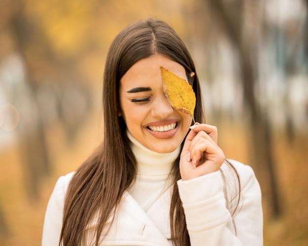 Jolie femme caucasienne souriante et tenant une feuille tombée à l'automne