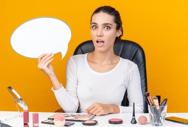 Jolie femme caucasienne surprise assise à table avec des outils de maquillage tenant une bulle de dialogue