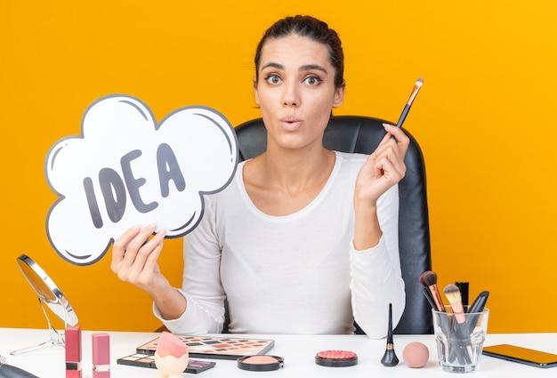 Jolie femme caucasienne surprise assise à table avec des outils de maquillage tenant une bulle d'idée et un pinceau de maquillage isolé sur un mur orange avec espace de copie