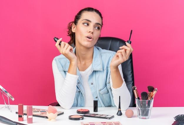 Jolie femme caucasienne surprise assise à table avec des outils de maquillage tenant et regardant un eye-liner isolé sur un mur rose avec espace de copie