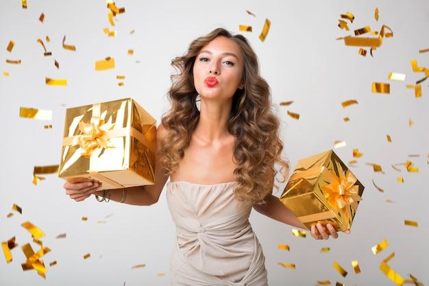 Jolie femme célébrant le nouvel an tenant des cadeaux