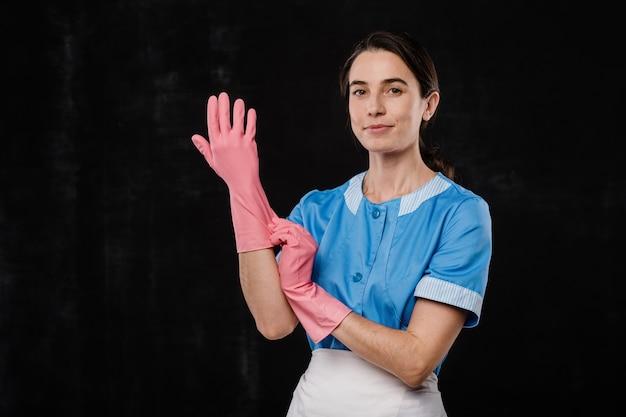 Jolie femme de chambre de mettre des gants en caoutchouc rose en se tenant debout devant la caméra sur fond noir