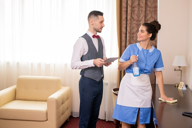 Jolie femme de chambre en table de nettoyage uniforme tout en regardant porter avec tablette pendant la conversation au travail dans l'hôtel