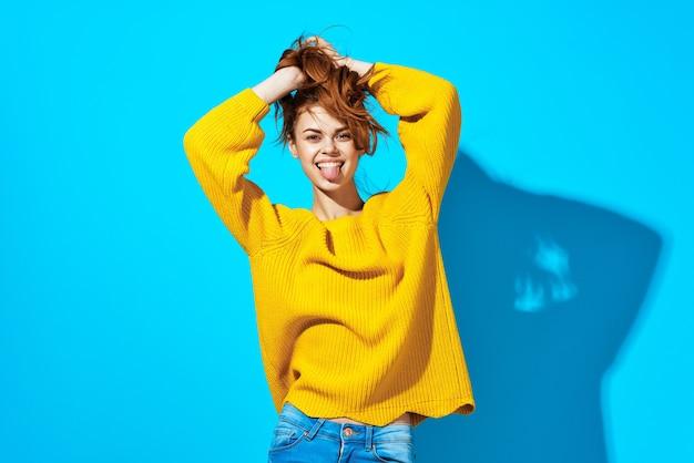 Jolie femme en chandail jaune émotions coiffure à la mode posant