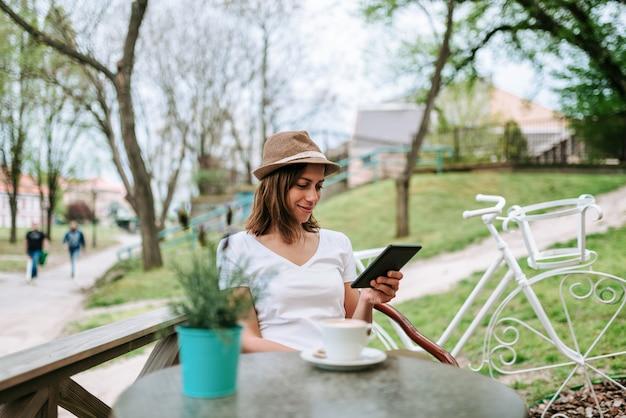Jolie femme avec un chapeau assis au café en plein air et à l'aide de tablette.