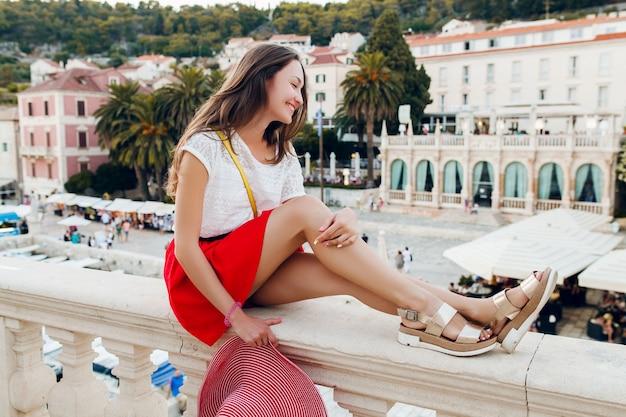 Jolie femme avec un chapeau rouge sur les jambes de vacances en sandales