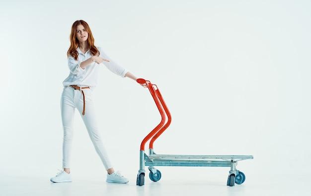 Jolie femme avec chariot shopping dans l'expédition de supermarché