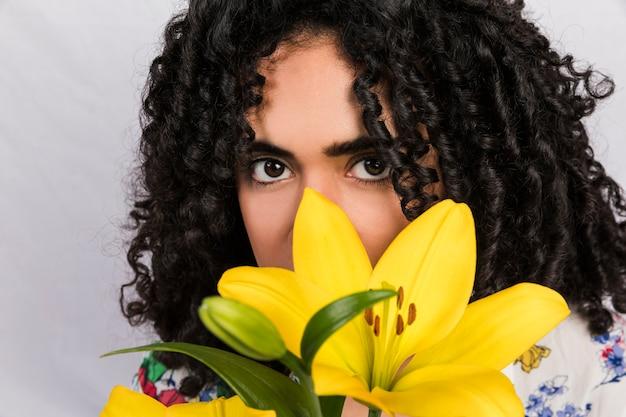 Jolie femme charmante ethnique avec fleur tropicale