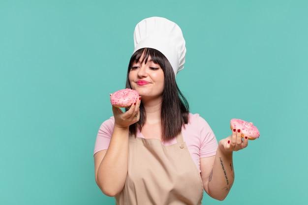 Jolie femme chef expression heureuse et tenant des beignets