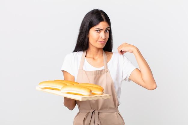 Jolie femme chef hispanique à l'air arrogante, réussie, positive et fière et tenant un plateau avec des petits pains
