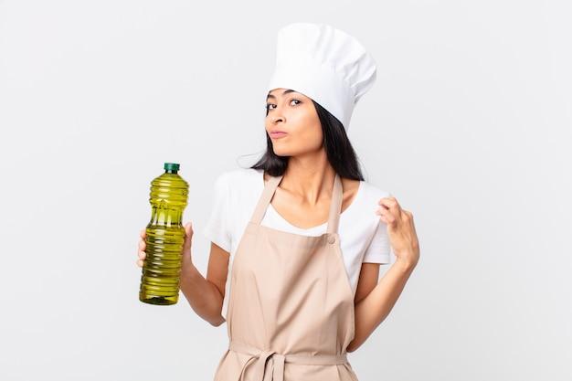 Jolie femme de chef hispanique tenant une bouteille d'huile d'olive.